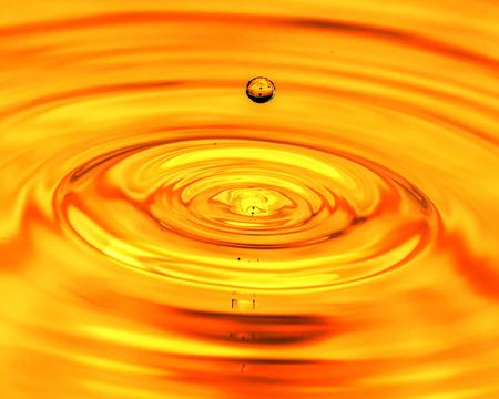 een druppel water valt in een gouden water. macro Stockfoto