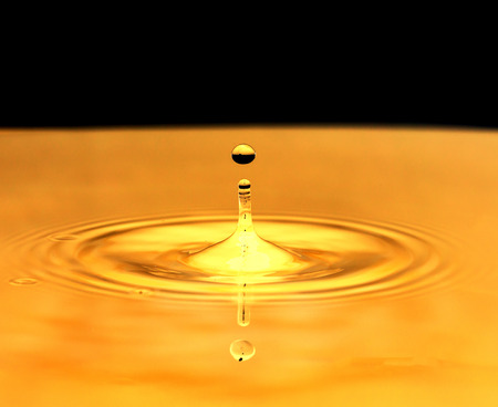 a drop of water falls in a golden water. macro photo