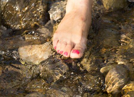 uñas pintadas: pedicure pie en el agua en las rocas