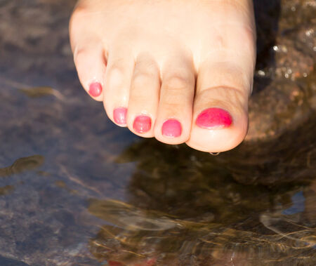 painted toes: pedicure on foot in the water on the rocks Stock Photo