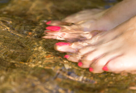 painted toenails: pedicure on foot in the water on the rocks Stock Photo