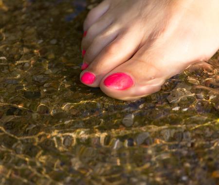 u�as pintadas: pedicure a pie en el agua en las rocas
