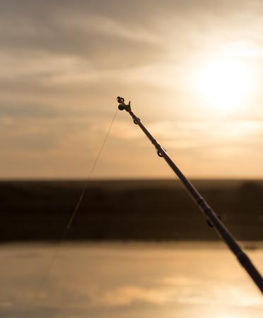 rod on the lake at sunset photo