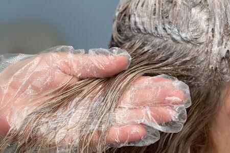 tinte de cabello: esteticista aplicar tinte para el cabello sobre el cabello cliente hembra