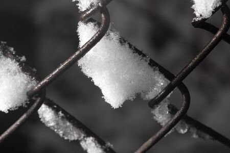 snow on the fence. close-up photo