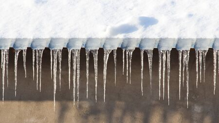 thawing: icicles which are hanging down from a roof.