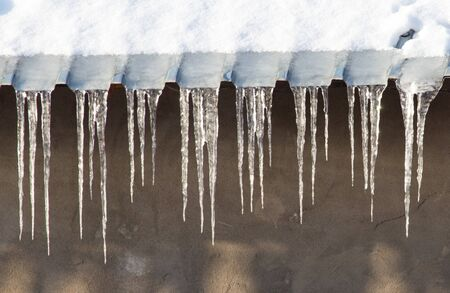 thawing: Icicles which are hanging down from a roof. Stock Photo