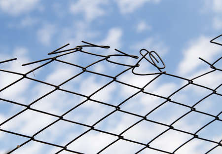 confined space: Metal fence against the blue sky with clouds Stock Photo