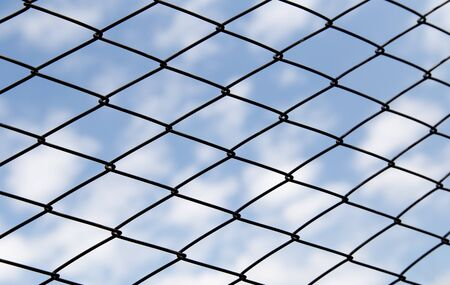 Metal fence against the blue sky with clouds photo