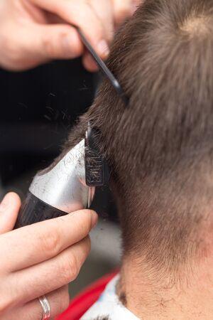 haircutter: Man having a haircut with a hair clippers Stock Photo