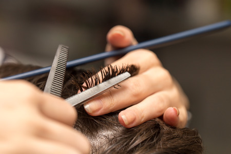 comb hair: mens hair cutting scissors in a beauty salon