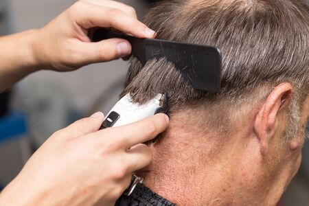 haircutter: Close up of a male student having a haircut with hair clippers