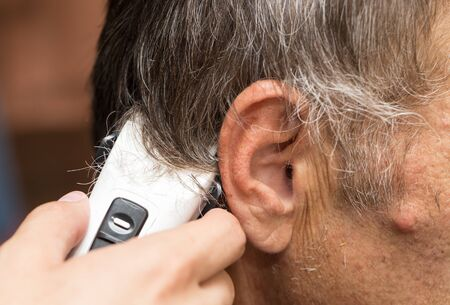 hair clippers: Close up of a male student having a haircut with hair clippers