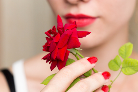 red hand: red rose, red manicure and red lips