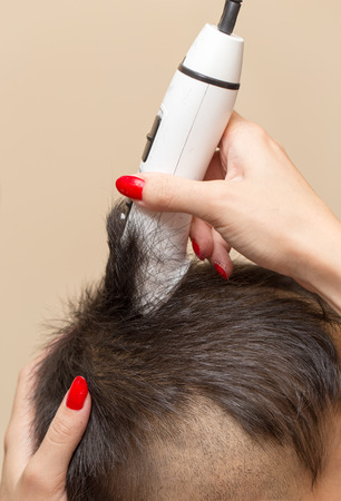 hair clippers: Man having a haircut with a hair clippers Stock Photo