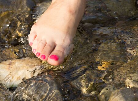 uñas pintadas: pedicure en pie en el agua en las rocas