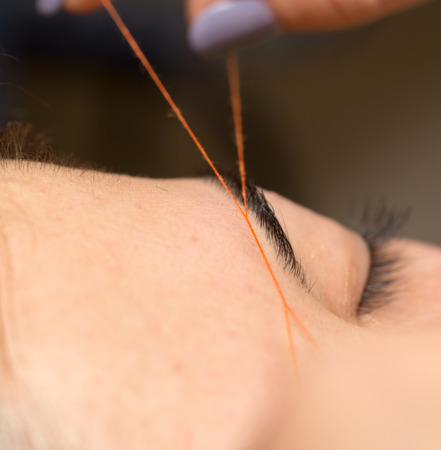 Grooming the eyebrows thread in a beauty salon. close