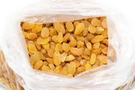 apricot kernels: yellow raisins in a plastic bag Stock Photo