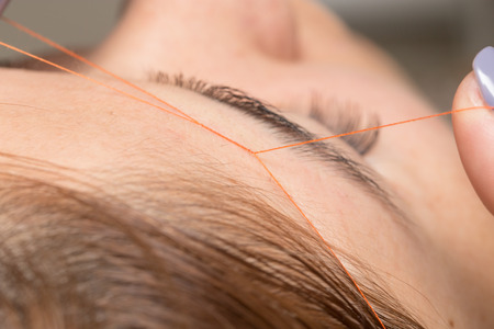 threading hair: Grooming the eyebrows thread in a beauty salon. close
