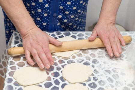 sheeting: Woman sheeting the dough with a rolling pin in the kitchen