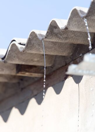 trickle down: Water from the roof of the house Stock Photo