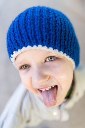curly hair child: portrait of a boy showing tongue Stock Photo