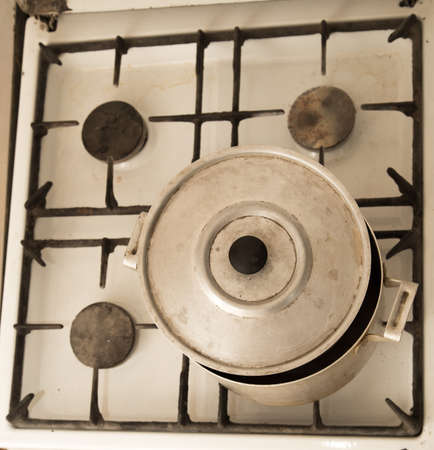 unhygienic: aluminum pan on old dirty gas stove Stock Photo