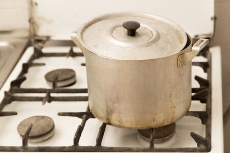 untidiness: aluminum pan on old dirty gas stove Stock Photo