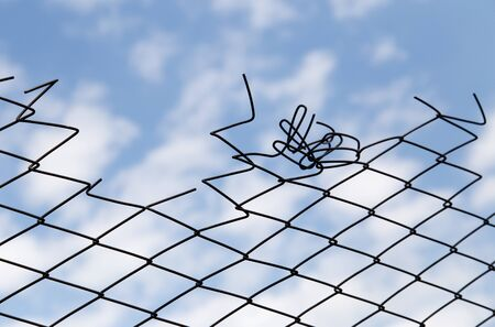 confined space: metal fence against the blue sky with clouds