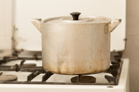 old gas stove: aluminum pan on old dirty gas stove Stock Photo