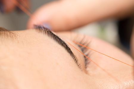 threading hair: Grooming the eyebrows thread in a beauty salon. close