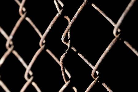 meshed: rusty metal grid on a black background Stock Photo