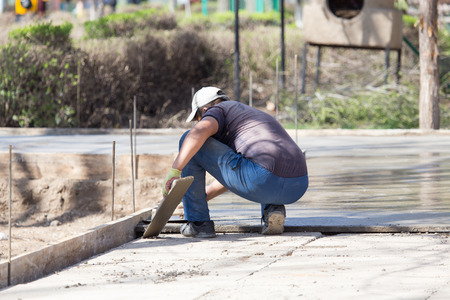 leveling: Construction workers leveling concrete pavement. Stock Photo