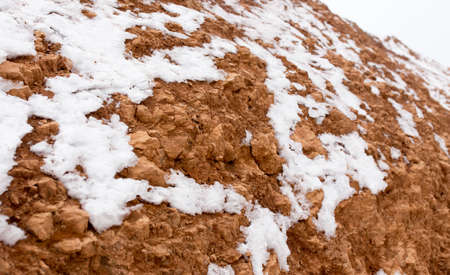 mud and snow: snow on red clay in nature