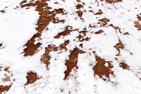 red clay: snow on red clay in nature