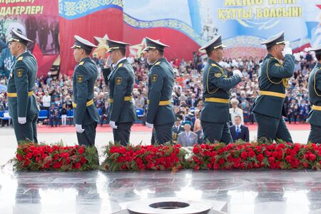 flower parade: SHYMKENT city, KAZAKHSTAN MAY 9, 2015: Laying flowers at the Eternal Fire, Victory Day, in memory of the soldiers of the Great Patriotic War. Victory Day celebration in the city of Shymkent, Kazakhstan May 9, 2015