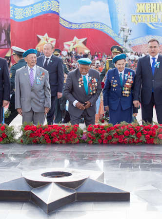 nazi flag: SHYMKENT city, KAZAKHSTAN MAY 9, 2015: Laying flowers at the Eternal Fire, Victory Day, in memory of the soldiers of the Great Patriotic War. Victory Day celebration in the city of Shymkent, Kazakhstan May 9, 2015