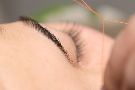 threading: Grooming the eyebrows thread in a beauty salon. close