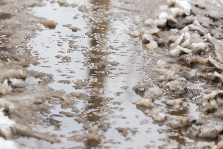 mud and snow: puddles from the rain in winter