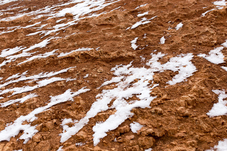 barrenness: snow on red clay in nature