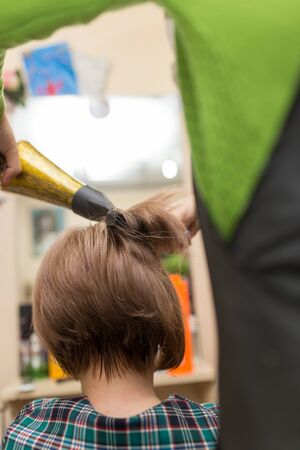Hairdresser dries the hair dryer blond  hair Stock Photo