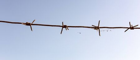 against: Barbed wire against the blue sky