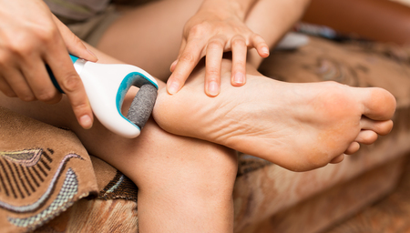footcare: girl cleans the heel on the foot Stock Photo