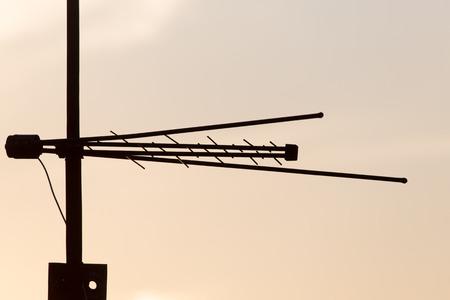 tv antenna: TV antenna on a background of dawn sun Stock Photo