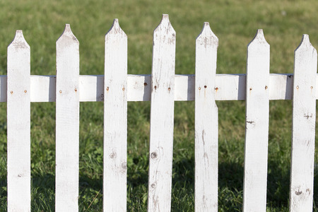 picket green: white wooden fence on nature Stock Photo