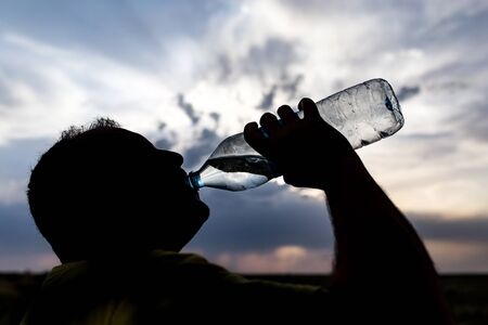man drinking water: silhouette of a man drinking water at sunset