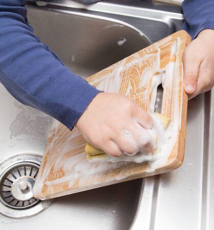 sink drain: boy washing dishes in the kitchen