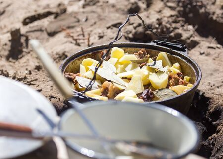 meat with potatoes in a cauldron on fire Stock Photo