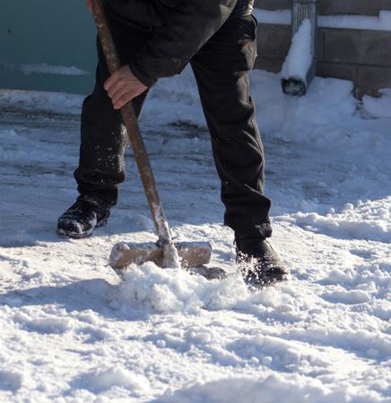 Worker cleans snow shovel