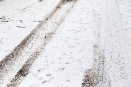 winter tires: traces of cars on the road in winter Stock Photo
